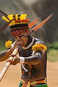 Xingu Indigenous Park, Mato Grosso State, Brazil. Aldeia Afukuri (Kuikuro). Festival of Taquara. Keinahu Kuikuro playing a taquara flute.