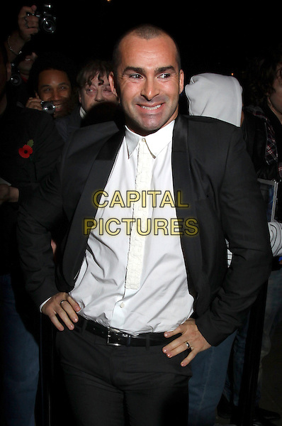 LOUIE SPENCE .Cosmopolitan Ultimate Women Of The Year Awards, Banqueting House, Whitehall Place, London, England. November 2nd, 2010..outside half length white shirt tie hands on hips smiling black jacket .CAP/AH.©Adam Houghton/Capital Pictures.