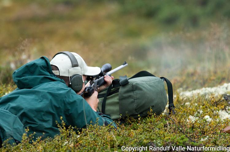 Mann skyter med anlegg mot ryggsekk ---- Man fires rifle