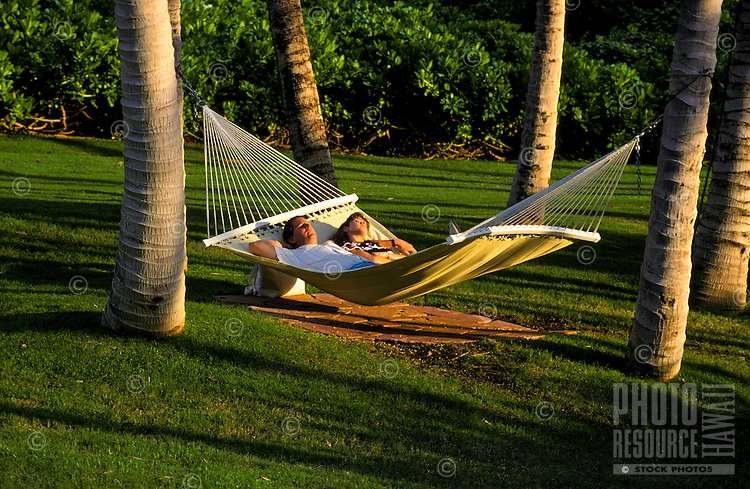 Couple in hammock strung on palm trees, with sunset lighting
