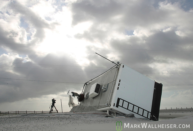 A mobile television broadcast truck, with it's abandoned camera still in place, lays on it's side July 11, 2005 in a road washout and covered with sand on Navarre Beach where Hurricane Dennis came ashore.