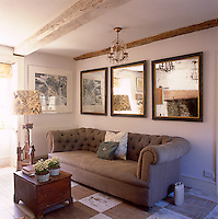 A white country sitting room with painted stone walls and a painted wood floor. Three mirrors hang on the wall above a Chesterfield sofa.