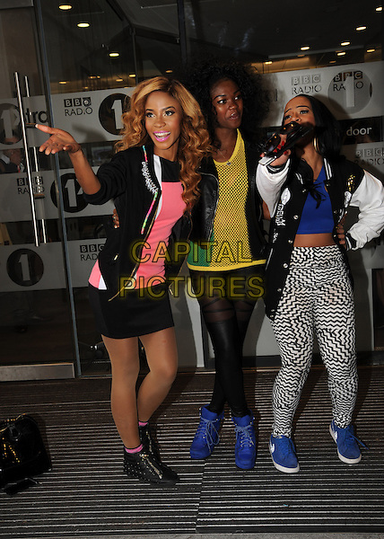 Miss Dynamix<br /> At BBC Radio 1, London, England.<br /> October 8th, 2013<br /> X Factor band group full length black jacket tights pattern white leggings skirt pink blue shoes hand finger pointing <br /> CAP/AOU<br /> &copy;AOU/Capital Pictures