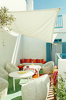 The second floor terrace is furnished with wicker tub chairs and a comfortable banquette and shaded by a simple awning