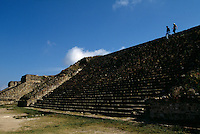 Tourists walk along the stairways at Monte Alban at the ruins of the ancient Zapotec capital overlooking the city of Oaxaca. First occupied around 500 BC by Zapotecs and development began with the building of temples and palaces.  At it's peak around 300-700 AD, the surrounding hills were terraced for dwellings and population was 25,000. It was a highly organized, priest-dominatea society. It was abandoned around 700-950 AD and used as burial grounds.