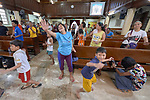 As children run around her, Mary Ann Miralden raises her arm as she sings during worship at Knox United Methodist Church in Manila, Philippines. The service is part of a weekday program where the church opens up to poor people in the neighborhood, offering showers, food, fellowship, and an opportunity to worship together.