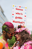 "29 June 2013, London, United Kingdom. Picture: Two gay men pose with a ""Guess who's getting married"" poster. Pride London 2013 parade starts with the motto ""love (and marriage)""."