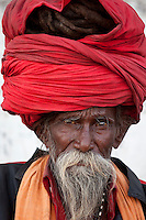 Hindu man pilgrim with long hair in turban at Dashashwamedh Ghat in holy city of Varanasi, Benares, India