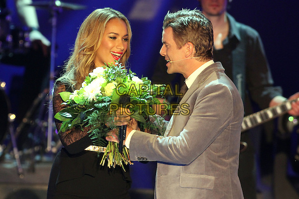 "Leona Lewis & show host Markus Lanz.Germany's biggest live TV-show ""Wetten Dass"", Offenburg, Germany..January 19th, 2013.half length black dress lace peplum gold belt on stage in concert live gig performance performing music grey gray beige suit flowers bouquet side profile .CAP/UNT.©Unit2/Capital Pictures"