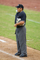 Home plate umpire Jose Esteras blows a bubble between innings of the South Atlantic League game between the Kannapolis Intimidators and the Hickory Crawdads at  L.P. Frans Stadium August 1, 2010, in Hickory, North Carolina.  Photo by Brian Westerholt / Four Seam Images