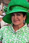 A woman in the Easter Parade in New York City wearing a large green hat