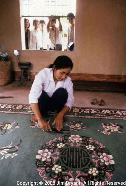 Hai Hung workers trim a hand-woven rung before it is prepared for export, They earn a little more than a dollar a day. Weavers turn out over 20,000 square meters of runs per year. The rugs are shipped to Europe, Canada and Iraq. (Jim Bryant Photo)..