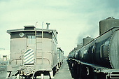 Alamosa yard scene with standard gauge caboose and train and narrow gauge tank cars.<br /> D&amp;RGW  Alamosa, CO