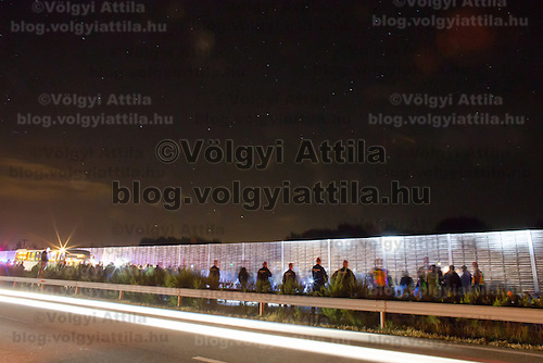 Long exposure photo shows illegal migrants walk with police escort on highway M5 after they broke out and run away from custody through a line of police officers near Roszke (about 174 km South of capital city Budapest), Hungary on September 07, 2015. ATTILA VOLGYI