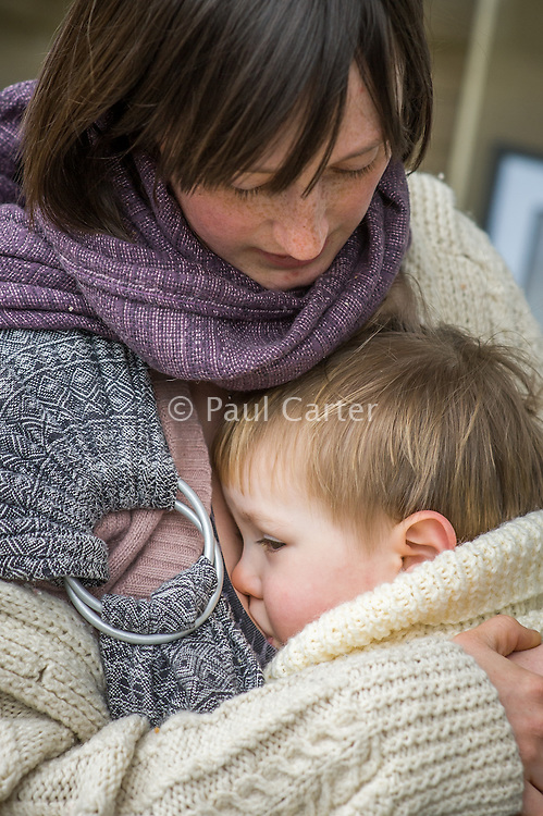 A mother breastfeeds her 15 month old boy who is in a sling.