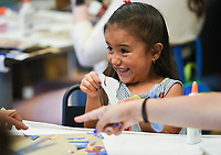 NWA Democrat-Gazette/CHARLIE KAIJO Ilaria Rios, 5, of Rogers reacts as she makes an art piece during a drop-in art making class, Sunday, July 7, 2019 at Crystal Bridges Museum in Bentonville. <br /> <br /> Guest artist, Michael Albert, showed guests how to make art using upcycled cardboard from discarded consumer packaging. The New York native is on a multi-state tour.