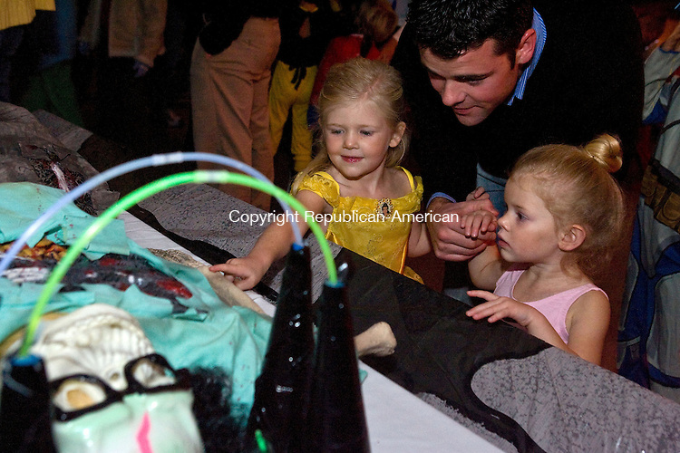 MIDDLEBURY, CT - 21 OCTOBER 2008 -102108JT03--<br /> Blake Barbarisi holds the hands of his daughters Tayden, 4, left, and Kali, 2, as they look at a fake skeleton during the Middlebury Public Library's &quot;Almost Haunted House&quot; on Tuesday. Tayden, of Middlebury, was dressed as Belle from &quot;Beauty and the Beast,&quot; while her sister was dressed as a ballerina.<br /> Josalee Thrift / Republican-American