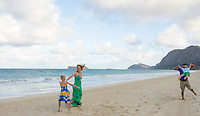 A family of four playing on Waimanalo Beach, O'ahu.