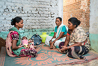 Rani Barukaum, the local SHG leader speaks with mother of a new born child, advising her on various health issues and the benefits of safe drinking water in Ambedkar Nagar in Medak, Telangana, India.