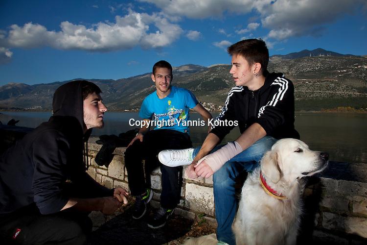 Greek students Dinos Athanasiou,18, (L) Christos Dimitriadis,18, (C) and Konstantinos Vartziotis,18, relax with their dog by the Ioannina lake.