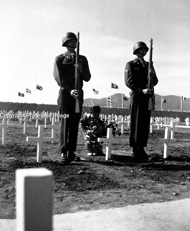 A little Korean girl places a wreath of flowers on the grave of an American soldier, while Pfc. Chester Painter and Cpl. Harry May present arms, at the United Nations cemetery in Pusan.  April 9, 1951.  Cpl. Alex Klein. (Army)<br /> NARA FILE #:  111-C-6425<br /> WAR &amp; CONFLICT BOOK #:  1522