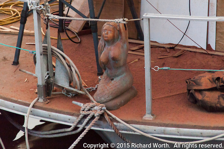 A pseudo-figurehead, the statue of a mermaid, crouches on the deck of a boat under repair.