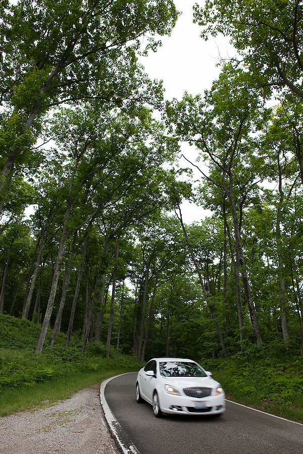 A car speeds along the Tunnel of Trees Scenic Heritage Route in summer, northwest Michigan near Harbor Springs, MI, USA