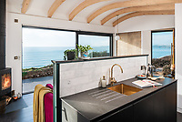 BNPS.co.uk (01202 558833)<br /> Pic: UniqueHomeStays/BNPS<br /> <br /> Pictured: There is a modern kitchen and living area with large sliding doors that make the most of the 180 degree views.<br /> <br /> A couple who spent £450,000 on turning a 'rotting shed' into an exclusive seaside bolthole hope to recoup their money - by renting it out for £3,150 a week. <br /> <br /> Tracey Gilpin and Peter Burridge went out on a limb when they bought the 60-year-old wooden shack for a whopping £220,000.<br /> <br /> Despite its ramshackle condition, the cabin could command such a hefty asking price as it is located halfway up a cliff with stunning views of Whitsand Bay in Cornwall.<br /> <br /> But in order to make the coastal chalet a viable holiday let the couple had to demolish it and build a new one from scratch.