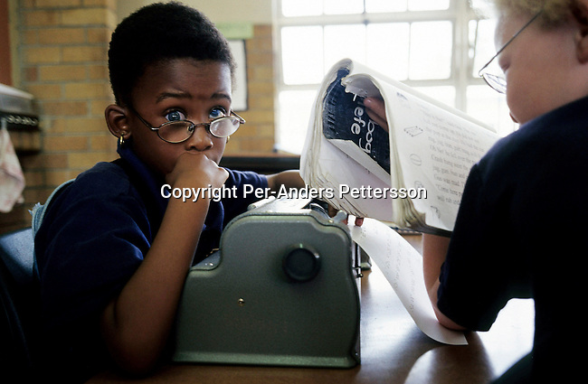 KLIPRIVER, SOUTH AFRICA APRIL 15: Boitumelo Dingalo, age 6, (L) and Relebogile Molefe, age 7, reads Braille during a class on April 15, 2003 at Sibonile (means: we have seen) School for the Blind in Klipriver, south of Johannesburg, South Africa. A blind woman founded the school in 1994. The school has about 125 students from disadvantaged communities around South Africa. Many of the children have faced rejection from their families and communities, and at Sibonile they have a chance for a good education. .(Photo: Per-Anders Pettersson)..