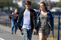 Pictured: A young couple walking during the sunny weather at Mumbles, near Swansea, Wales, UK. Thursday 19 September 2019