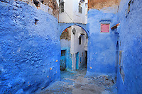 Narrow stepped street painted blue with an overhead archway and a decorative hanging lamp, in the medina or old town of Chefchaouen in the Rif mountains of North West Morocco. Chefchaouen was founded in 1471 by Moulay Ali Ben Moussa Ben Rashid El Alami to house the muslims expelled from Andalusia. It is famous for its blue painted houses, originated by the Jewish community, and is listed by UNESCO under the Intangible Cultural Heritage of Humanity. Picture by Manuel Cohen