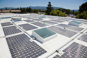 Solar panels and skylights on a commercial office building roof in Silicon Valley. The Santa Cruz Mountains a visible in the distance. San Jose, California, USA