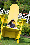 Woman in large yellow wooden chair.