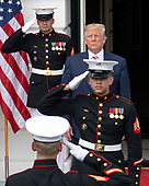 The Marine Guards salute as United States President Donald J. Trump emerges from the Diplomatic Entrance of the White House to welcome President Klaus Iohannis of Romania in Washington, DC on Tuesday, August 20, 2019.<br /> Credit: Ron Sachs / CNP
