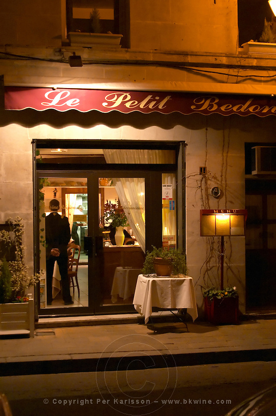The restaurant Le Petit Bedon at night with the waiter standing inside the door.  Avignon, Vaucluse, Provence, Alpes Cote d Azur, France, Europe