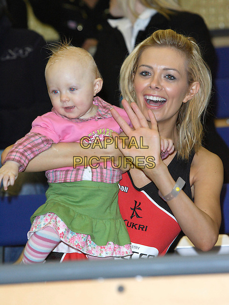 ORLAITH McALLISTER & EVA.Celebrity Netball 7's, SPACE Sports Centre, Hackney, London, England..November 18th 2007.sevens court team sport playing game charity half length big brother red top baby child infant pink skirt green mother mom mum family hand palm waving mouth open .CAP/ROS.©Steve Ross/Capital Pictures