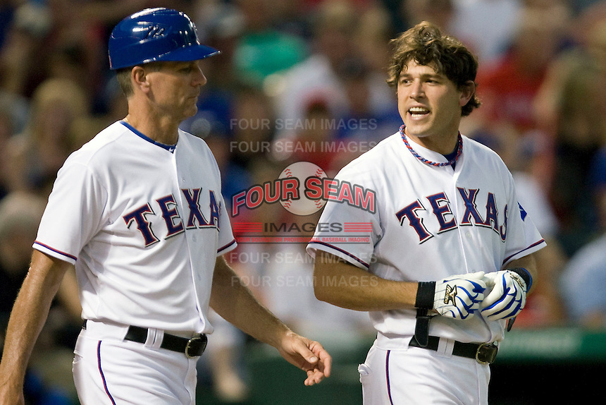 Texas Rangers second baseman Ian Kinsler #5 disagrees with a called third strike as Rangers first base coach Dave Anderson shields him from the umpire during the Major League Baseball game against the Texas Rangers at the Rangers Ballpark in Arlington, Texas on July 27, 2011. Minnesota defeated Texas 7-2.  (Andrew Woolley/Four Seam Images)