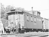 End-side angle view of long caboose 04343, flying herald, round roof with two unidentified men posing at end.<br /> D&amp;RGW  Alamosa, CO  Taken by Richardson, Robert W. - 7/4/1941