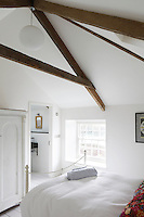 Low ceilings have been removed to reveal the original wooden beams of the cottage which form a feature of the master bedroom