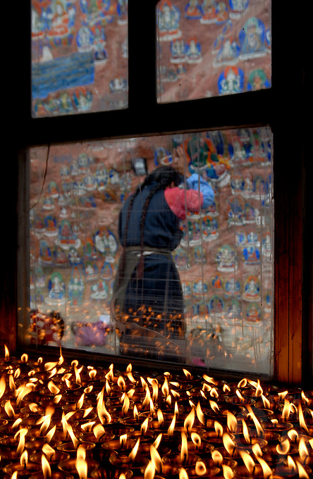 Butter lamps and a view through the window a Pilgrim facing the images of a thousand Buddhas, near Lhasa,Tibet, Yaowang Mountain