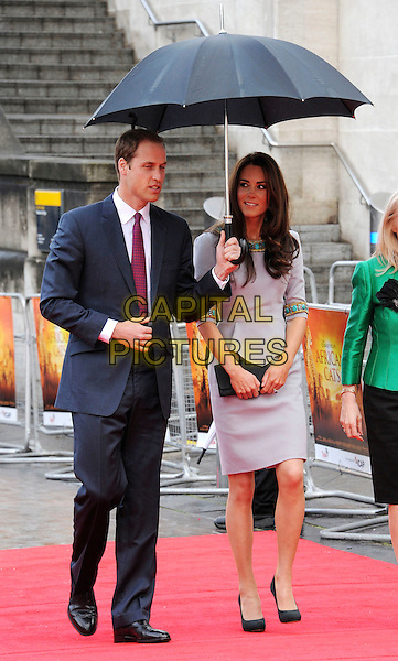 Prince William, Duke of Cambridge and Catherine, Duchess of Cambridge.'African Cats' UK Premiere at BFI Southbank, London, England..25th April 2012.full length kate royals royalty married husband wife blue suit grey gray dress turquoise gold beads beaded umbrella clutch bag.CAP/WIZ.© Wizard/Capital Pictures.