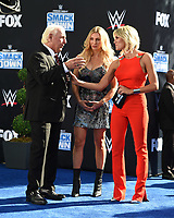 """LOS ANGELES - OCTOBER 4: Charissa Thompson speaks to Ric Flair and Charlotte Flair during the kick-off event for the """"WWE Friday Night Smackdown on FOX"""" at Staples Center on October 4, 2019 in Los Angeles, California. (Photo by Frank Micelotta/Fox Sports/PictureGroup)"""
