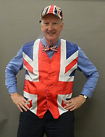 BNPS.co.uk (01202 558833)<br /> Pic: BNPS<br /> <br /> Roddy Lloyd of Rowleys auction house in Cambridge, dressed in some of John McCririck's clothes.<br /> <br /> The widow of the late racing pundit John McCririck is selling off his wardrobe of clothes and jewellery.<br /> <br /> The TV personality was known for wearing deerstalker hats, flamboyant suits and oversized gold rings as he delivered the betting news at the races on Channel 4 for years.<br /> <br /> He did July aged 79 and now his widow Jenny has decided to put some of his possessions up for sale.<br /> <br /> She said part of the reason was that she was worried thieves would target her because of the jewellery that her husband was famous for wearing.