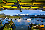 Alaska Marine Highway System Matanuska sailing through Wrangell Narrow to Petersburg, SE Alaska on a sunny day.  Passengers on deck chairs.  Snow capped mountain in the background.