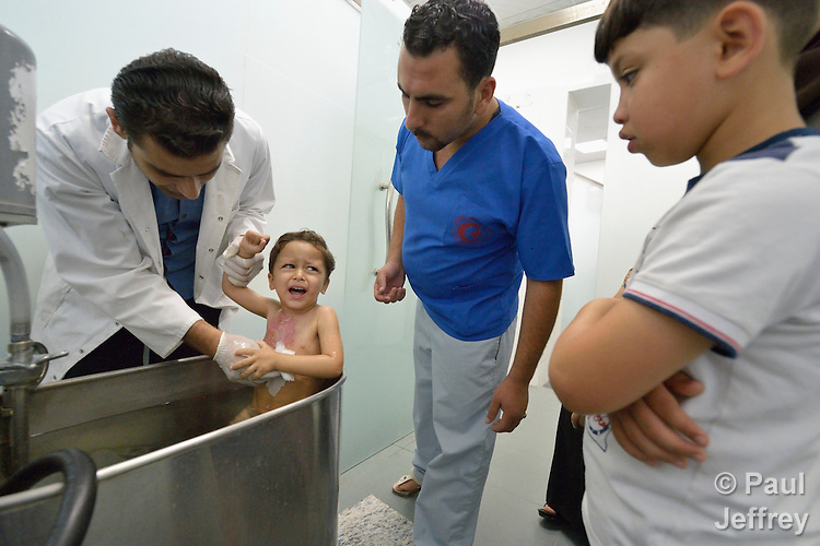 Three-year old Anas, who suffered a severe burn to her chest, is treated by Dr. Mohannad Hadad as the girl sits in a therapeutic bath in the Al Ahli Arab Hospital in Gaza City. The Anglican Church-affiliated hospital is a member of the ACT Alliance.<br /> <br /> The 2014 war provoked serious damage to Gaza's health infrastructure. Seventeen hospitals, 56 primary health care facilities and 45 ambulances were damaged or destroyed. Sixteen health care workers were killed and 83, most of them ambulance drivers and volunteers, were injured.<br /> <br /> Parental consent obtained.