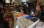 Palestinians gather at a shop selling chocolate at a store a few days ahead of Eid al-Fitr holiday in Gaza city on June 2, 2019. Eid al-Fitr marks the end of Muslim's holy fasting month of Ramadan when faithfuls abstain from eating, drinking, smoking and sexual activities from dawn to dusk. Photo by Ashraf Amra