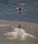 Cal Fire helicopter 404 picks up water from Priest Reservoir at the Flat Fire started on Highway 49 near Moccasin and burned up hill toward Priest Dam. Photo by Al Golub
