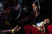 Rekha Devi, the local village health worker speaks with Devi in her hut in Bhelaiya village in Raxaul, Bihar, India.