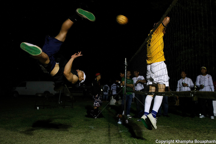 Loui Tiengthong of Minneapolis, Minnesota, left, attempts a roll spike during a kator tournament during the Lao New Year celebration at Wat Lao Thepnimith in Fort Worth on April 24, 2010.  (photo by Khampha Bouaphanh)