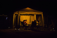 Switzerland. Canton Ticino. Tenero. Camping Campofelice. Electric lights at nighttime. People talk together under a tent in the evening hours. A caravan, travel trailer, camper or camper trailer is towed behind a road vehicle to provide a place to sleep which is more comfortable and protected than a tent. It provides the means for people to have their own home on a journey or a vacation. Campers are restricted to designated sites for which fees are payable. 19.07.2018 © 2018 Didier Ruef